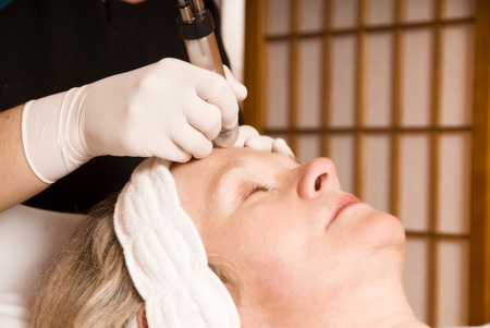 older woman: older woman getting electrolysis on he face