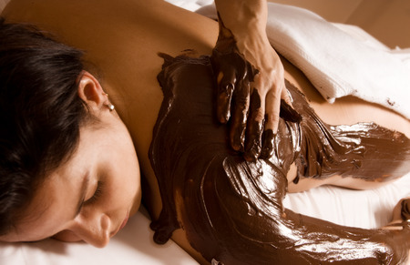 treatment: young woman getting a chocolate massage at a spa