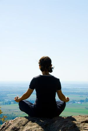 newage: Woman on the top of a mountain meditating