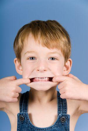 grimace: little boy doing a grimace in blue background