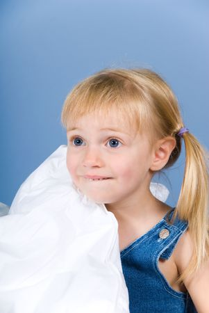 little cute blond girl on a blue wall photo