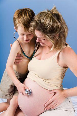 Cute blonde Junge hört das Kind im Mutterleib Standard-Bild - 1986219