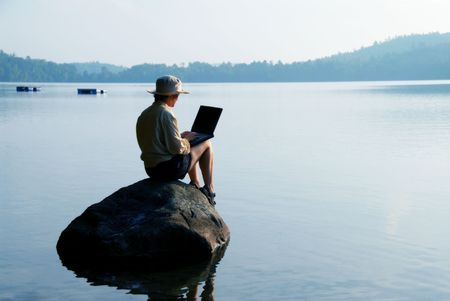laptop: woman on a rock with a laptop in nature Stock Photo