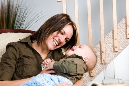 family tickle: mom resting in a chair with her baby Stock Photo