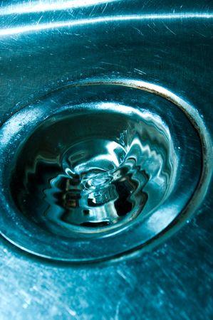 sink drain: water falling down the drain of a metal sink