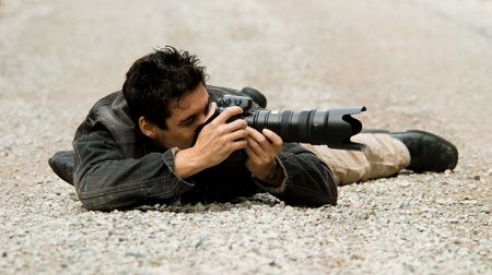 paparazzi photographer hiding on the ground to get shot