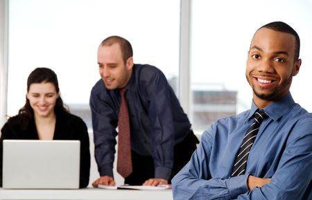 three business associates with a grey laptop Stock Photo - 2876265