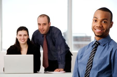 three business associates with a grey laptop photo