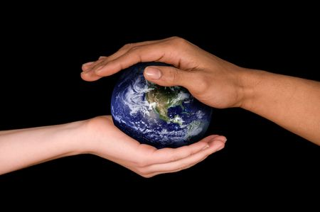 two hands holding a planet earth on black photo