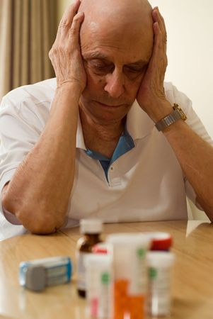 elderly man with all his pills and drugs