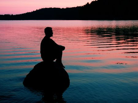 man on a rock at sunset on water