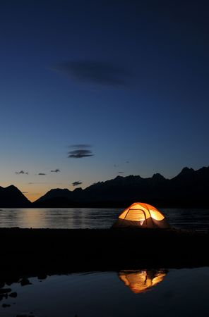 Evening lit tent in camping by nature photo