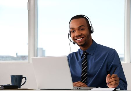 african business: Customer Service agent in an office with laptop Stock Photo