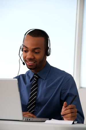 Customer Service agent in an office with laptop Stock Photo