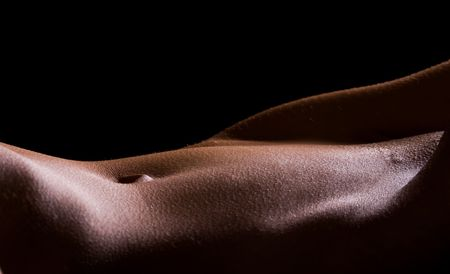 Female Tummy in the nude on black background