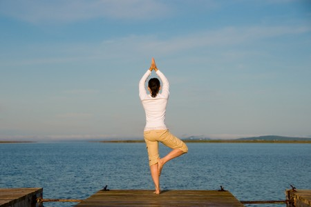 qigong: Yoga Woman on a dock by the ocean