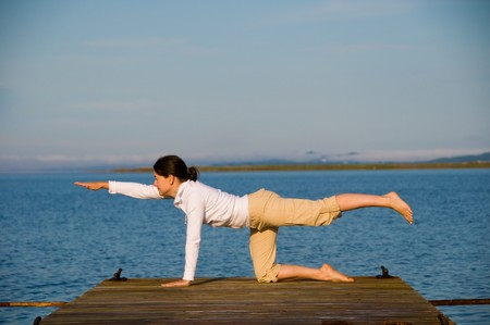 Yoga Woman on a dock by the ocean photo