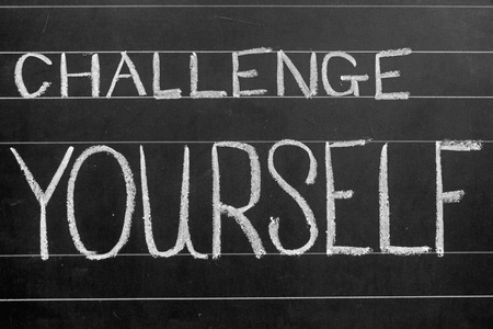 challenge yourself phrase handwritten on black chalkboard photo