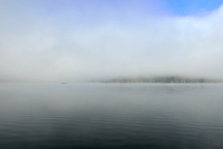 Landscape view of a lake with fog covering and a boat