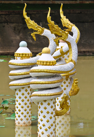 Golden-white Naga sculpture on pond in Lao temple, Laos