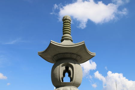 humankind: View of a stone carved lantern shape under the clear blue sky