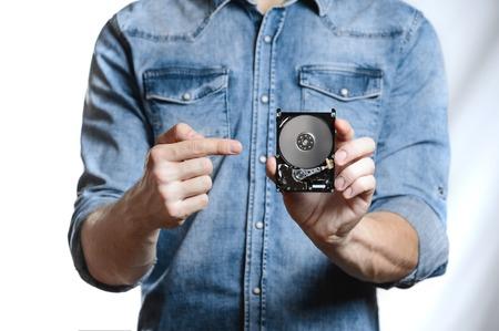 사람의 손에는 2.5 인치 하드 드라이브가 있습니다. 그는 하드 디스크를 가리 킵니다. PCB에서 후면 HDD보기. 흰색 배경에 고립. 스톡 콘텐츠