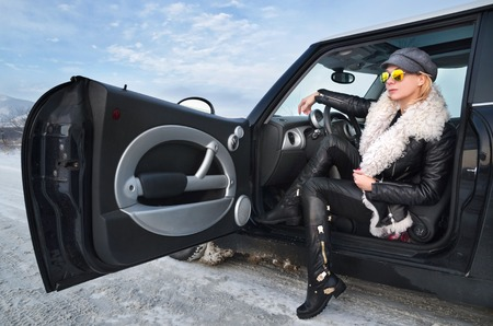 cooper: Hipster woman in sunglasses sitting in a small car in winter