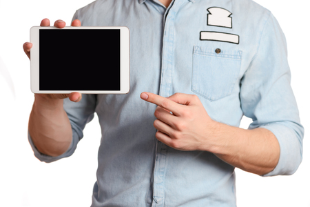 all right: A man in a light blue shirt and jeans with a brown belt is holding tablet pc isolated on white background, pointing to the screen tablet PC, showing all right