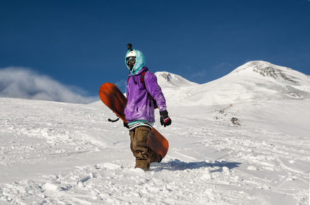 Snowboarder stands and walks on mountain slopes of an extinct volcano Elbrus