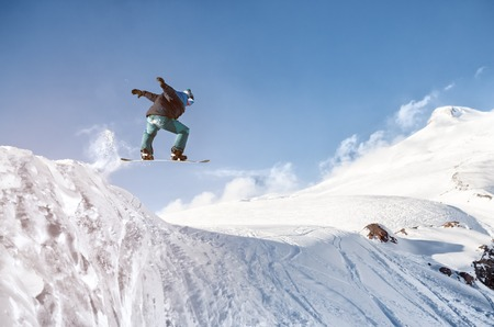 Stylish snowboarder with helmet and mask jumps from high snow slope Stock Photo