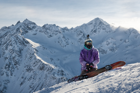 Snowboarder is sitting on mountain slopes of an extinct volcano Elbrus