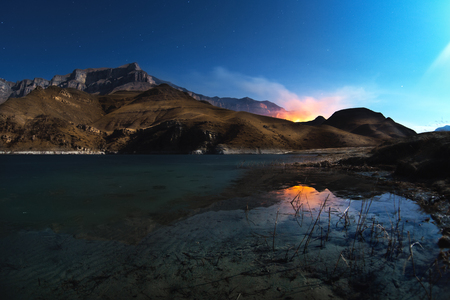 stargaze: A beautiful night landscape with a reflection of rocks in a mountain lake with the burning mountains in the background