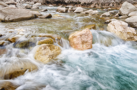 A river of fresh water among the rocks. Fresh aqua fast flow in the stones. A forest river with clean cold water. Fresh spring in the mountains. Concept of drinking water Stock Photo