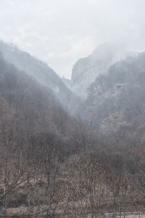 Low cloudiness with a fog in the winter mountains