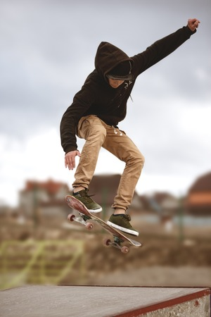 Close up of a skateboarders feet while skating active performance of stunt teenager shot in the air on a skateboard in a skate park Foto de archivo