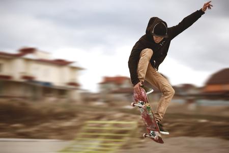 Cerca de los pies de un skater mientras patinan la actuación activa de truco adolescente disparo en el aire en una patineta en un parque de patinaje Foto de archivo - 74565524