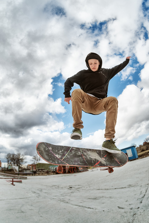 A young skateboarder makes Wallie in a skatepark, jumping on a skateboard into the air with a coup Stock Photo