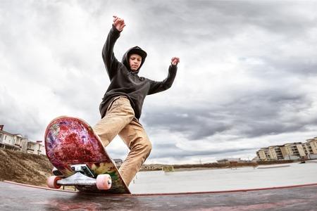 Patinadora adolescente en una sudadera con capucha y pantalones vaqueros se desliza sobre un pasamano en una patineta en un parque de patinaje Foto de archivo - 74647097