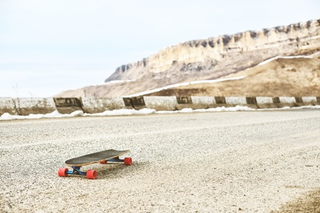 A lonely old longboard on a mountain serpentine, an asphalt road against a backdrop of mountains