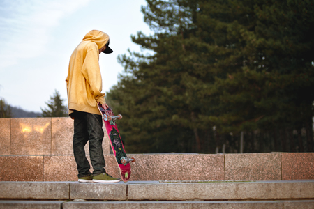 blacktop: The boy is standing with a skateboard in the sunset lights Stock Photo