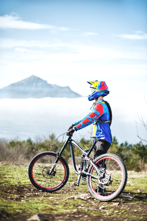 A young guy standing on your mountain bike atop a mountain, when below the mountains low clouds