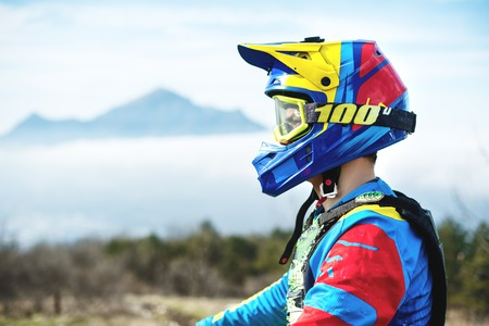 Portrait of a bicyclist in a full-face helmet and sunglasses against a background of a mountain