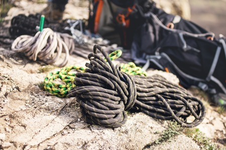 A neatly folded climbing rope lies on a rock