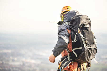 Close-up of a climber from the back in gear and with a backpack with equipment on the belt, stands on a rock, at high altitude