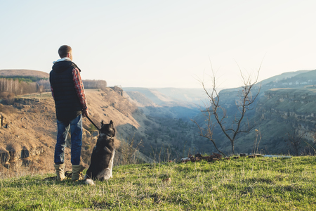 A man with a beard walking his dog in the nature, standing with a backlight at the rising sun, casting a warm glow and long shadows against the background of the gorge and trees. Stock Photo