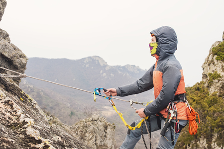 The Young Man climbs the rock on a rope with safety belts, insurance and rope, in full mountaineering equipment and a helmet Stock Photo