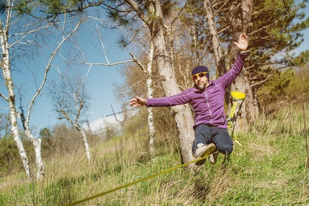 A man at the age of sitting in glasses with a hat and sneakers on the slackline, catches balance and enjoys life on the nature in the park