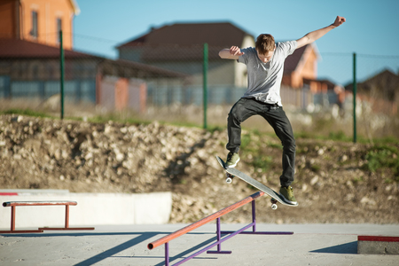 Teen skater In a gray T-shirt and headphones and jeans slides over a railing on a skateboard in a skate park