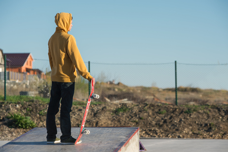 Teenager standing in a yellow hoodie holding a hand skateboard on the background urban slum