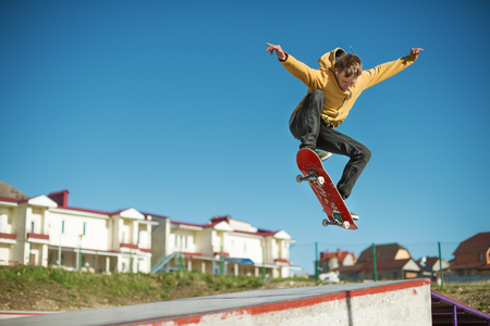 A teenager skateboarder does an ollie trick in a skatepark on the outskirts of the city